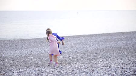 заботливый : two sisters running around the stony beach holding hands, children dressed in a dress Стоковые видеозаписи