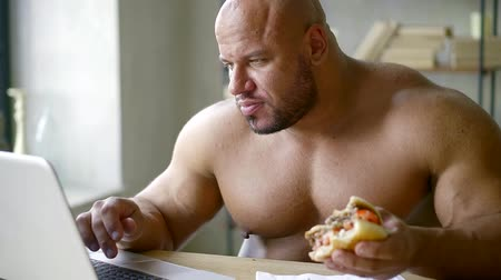 ízléses : male athlete with big muscles sitting at the table working on laptop and eating triple Burger with beef Patty