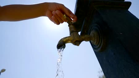 csőhálózat : close up shot of a womans hand, who opens a faucet from which water flows Stock mozgókép