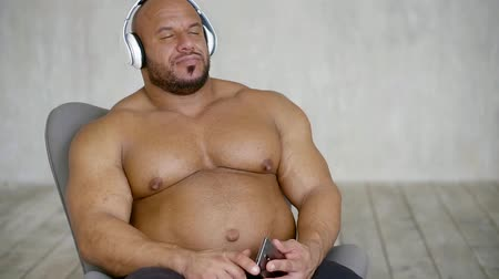 favori : bodybuilder man sitting in a chair and listening to your favorite music in wireless headphones