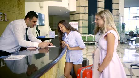 zkontrolovat : Three beautiful women check-in at hotel for summer. Female tourists with baggage on hotel reception. Arrival.
