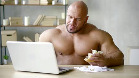 ízléses : bald male bodybuilder writes text on a laptop and does not violate the diet eats a triple Burger with beef Patty