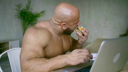 hármas : big male bodybuilder prints the text on the computer and follow a diet Burger with triple beef Patty