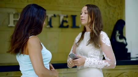 lobby : Two female friends meet on hotel reception.