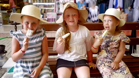 headwear : Portrait of three cute funny girls in hats licking ice cream sitting on the bench indoor.