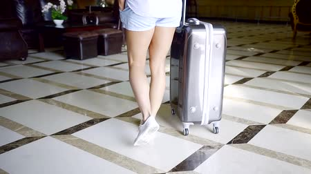 bagagem : Woman arriving in a hotel with suitcase on vacation.