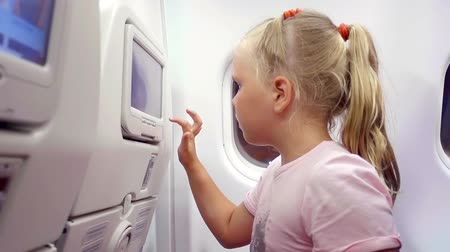lugares sentados : Close up shot of a little blonde cutie playing with touchscreen in plane seat.