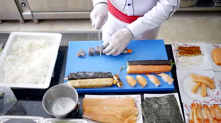 nori : master sushi is cutting rice rolles on plastic board in kitchen of japanese restaurant, top view