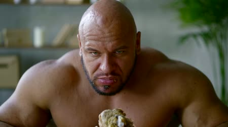 sağlam : close-up of bald bodybuilder chewing meat from fried leg, holding it in hand and biting, hungry muscular man