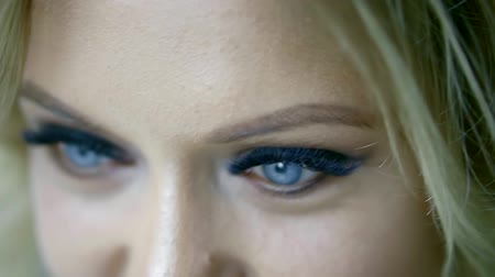 looking down : close-up view of beautiful female blue eyes with vivid makeup and fake lashes, woman is looking