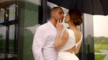 hozzábújva : sexual slim woman is cuddling to tall strong man, stroking his body, pair is standing under umbrella outdoors in rainy day, man is leaning on wall of building