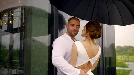 seducing : couple in the summer rain in the daytime, a man hugs his girlfriend and holds an umbrella