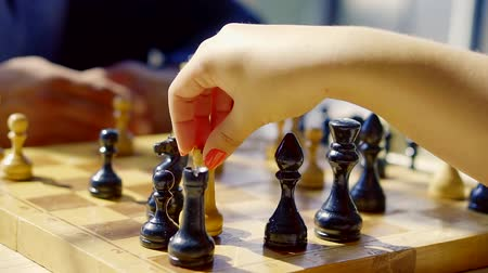 šachy : close up shot of a womans hands, who plays chess, she has a strong opponent