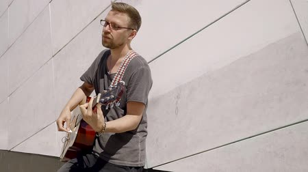 nejlon : handsome young man in glasses and a beard playing the guitar. he enjoys the sound of a musical instrument. the wind blows on a Sunny summer day