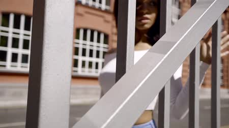 téma : movement along the iron fence. a young African American girl in white topic is touching the edge of the metal Dostupné videozáznamy