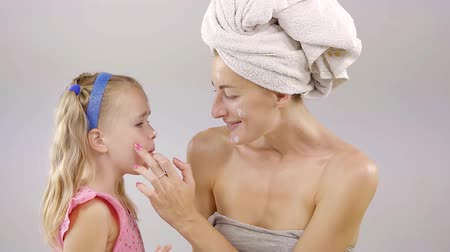 ostoba : Mother-daughter treatment. Mother decides to apply some cream on her daughter face while being silly and laughing