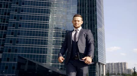 odráží : Young, handsome and confident businessman is having a walk on the way to work Dostupné videozáznamy