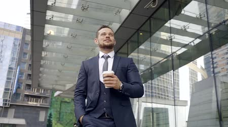 elszánt : Successful dedicated young businessman is walking on street among skyscrapers in business district wearing three-piece suit, tie and drinking hot black coffee