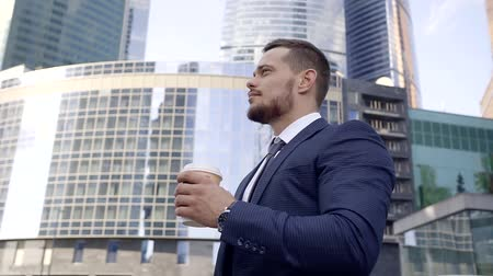 napój : Yougn and attractive businessman is having a coffee for breakfast before starting hard-working day.