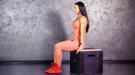 quadriceps : girl athlete performs an exercise of leg extension sitting on a chair. training the muscles of the thigh quadriceps Stock Footage