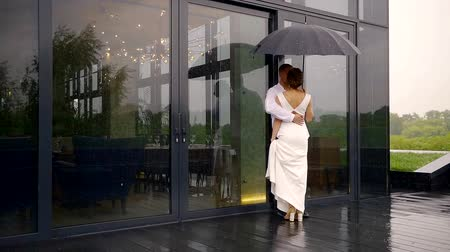 juntar : the man and his bride stand with an umbrella in the rain, the couple communicate with each other