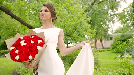lem : a young bride stands on the nature in a wedding dress, in her hand have bouquets of roses