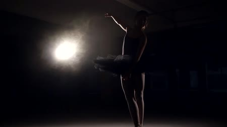 строгий : Ballerina is practing her moves in dark studio.