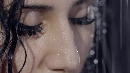 duygusallık : close up shot of the womans face with black eyelashes and big eyes, on whom the water falls