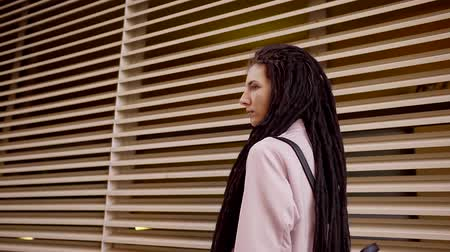dread : A young woman with long dreadlocks on her head goes along the fence, on her back a briefcase Stock Footage