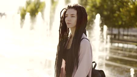 dread : A young and pretty woman with dreadlocks on her head strolls along the fountains on a summer day Stock Footage