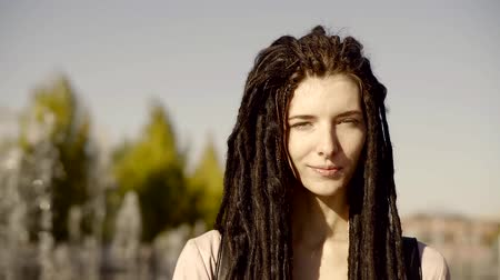 rendkívüli : A young and pretty teenager with dreadlocks walks along the street on a summer day