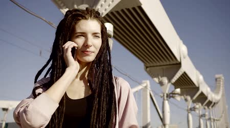 pankáč : Portrait of modern woman with dreadlocks on her head who is talking to friends on her mobile phone