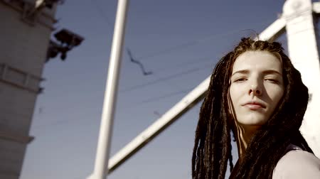 dread : A young and stylish woman with dreadlocks walks against the backdrop of urban buildings