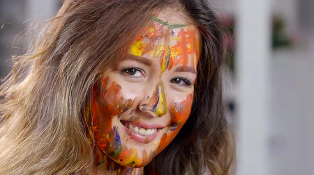 face painting : Portrait of a woman with a brightly painted face, a lady with makeup smiling happily and touching her chin