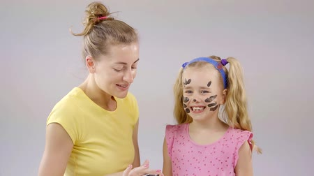 lion : A little girl is playing with her mom, a woman is applying paint on her face in order to draw a pets face Stock Footage