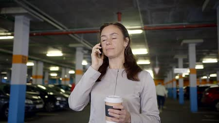 go away : An adult woman who is in an underground parking zone is talking on her mobile phone Stock Footage