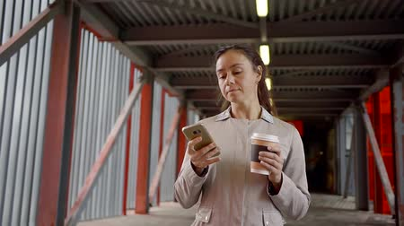 go away : Young woman with a take-away coffee in her hand reads a message on her mobile phone