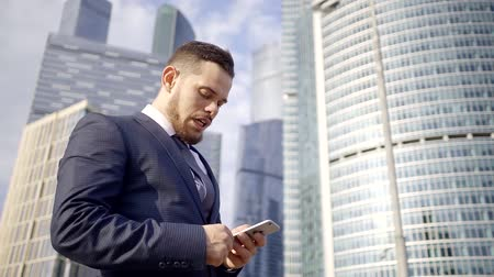 negotiations : A young and serious man with a beard reading brokerage news in an online newspaper on a mobile phone Stock Footage