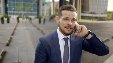 kívül : A young and handsome man who looks like a businessman, talks on mobile telephon with investors