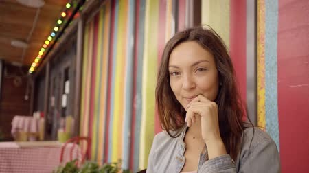 denim : A young and attractive woman with brown eyes looks thoughtfully, the lady is in a romantic cafe Stock Footage