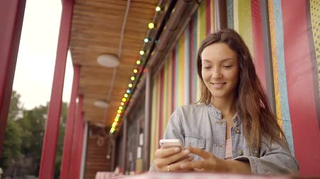 correspondência : a pretty woman is holding a mobile phone and communicating with friends in social networks on a smart phone