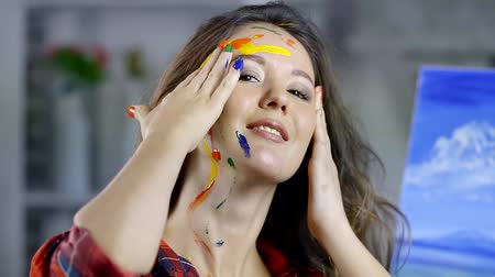 face painting : cute young girl with beautiful long hair celebrating writing oil painting in my Studio. gentle fingers paint the face with different colors of paint