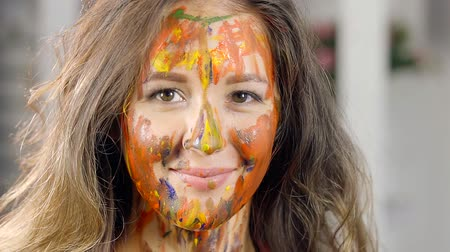 greasepaint : close-up. portrait of charming girl with a beautiful smile. face in different colors of oil paint Stock Footage