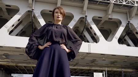 гот : Stylish woman goth is dark clothes with hands resting at the sides on the background of railway bridge on a Sunny day