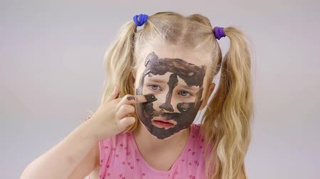 meio : cheerful little girl with white hair plays with a mask of black clay for the face. causes the finger means to care for skin Stock Footage