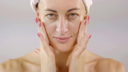turban : Beautiful woman applying skincare lotion to face caring for skin with feminine beauty products. portrait. close-up.
