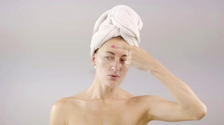 vanity : successful young girl playfully dancing after a shower with a turban out of a towel and the finger gets white cream on her forehead