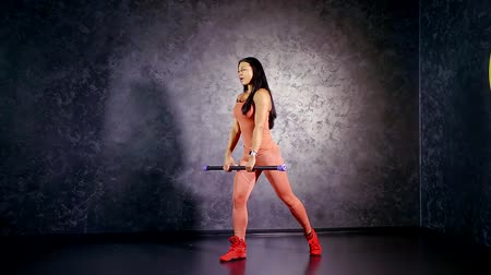 multifunctional : young girl athlete teaches to perform the exercise deadlift on one leg with a bodibar in his hands. muscle group of the glutes and hamstrings