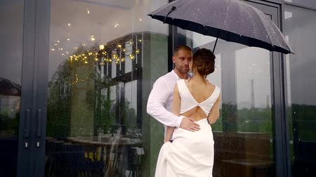juntar : a man and his beautiful bride dressed in a white wedding dress are standing together under an umbrella, its raining outside, and the newlyweds are hugging and talking to each other