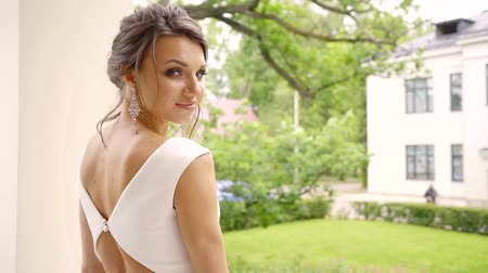 lem : young and beautiful bride with a natural make-up stands on the street in a wedding dress, a lady looks in the distance in the hope of seeing her husband Dostupné videozáznamy